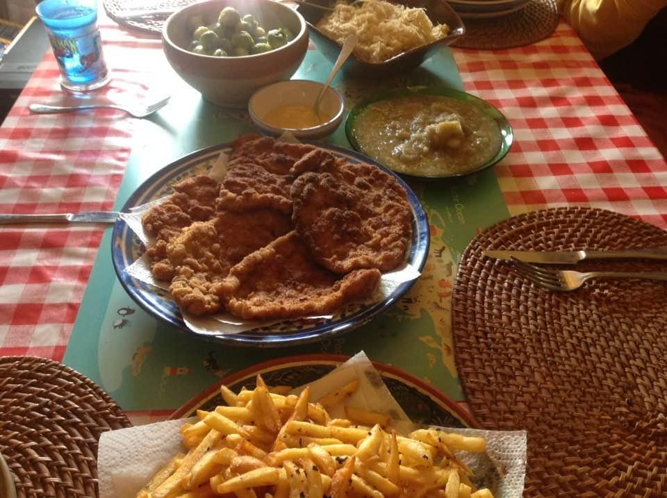 Homemade schnitzel with fries, sauerkraut, apple sauce and Brussels