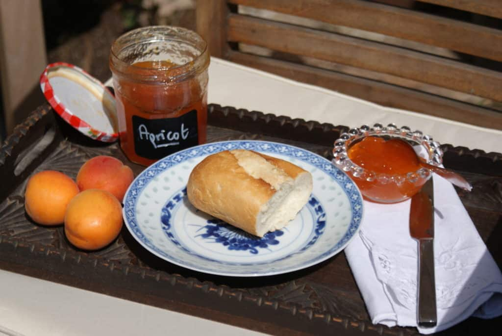 a small glass dish of apricot jam, on a wooden tray