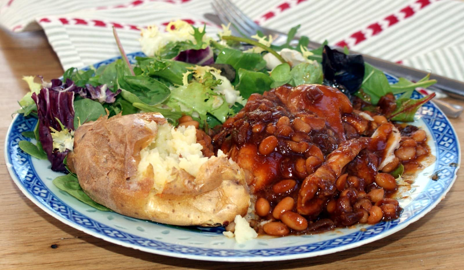 Honey and Soy chicken on a blue patterned plate with baked potato and sala