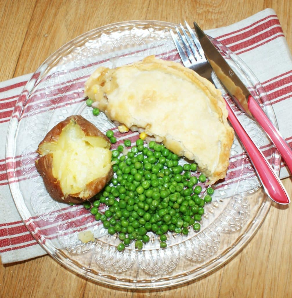 bacon and sweetcorn pie, on a glass plate, with a baked potato and green peas
