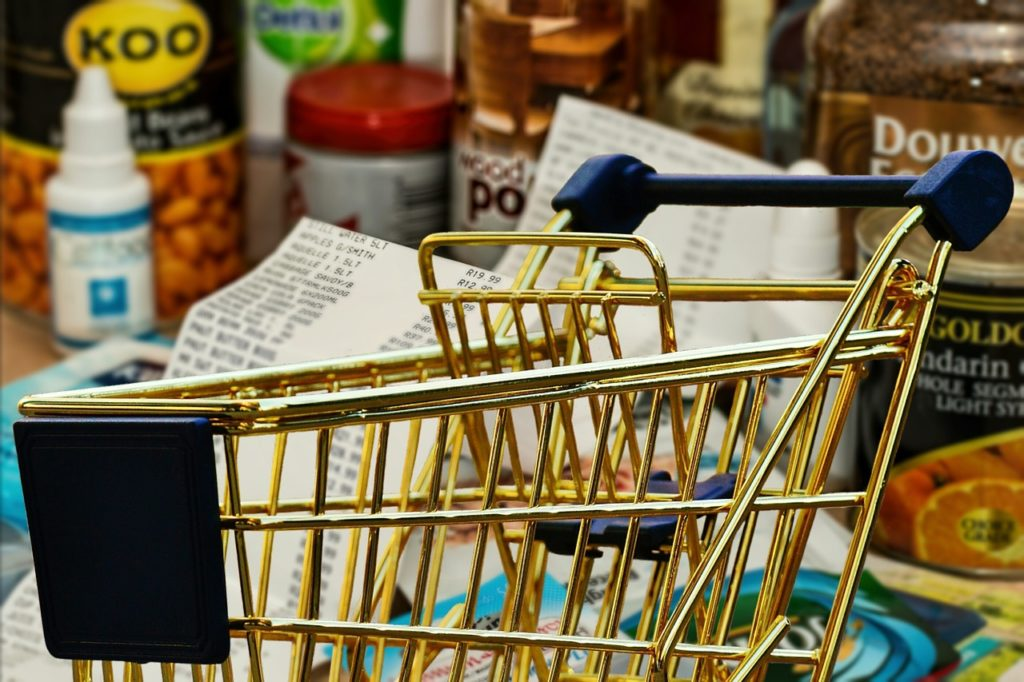 A shopping cart, with groceries in the background